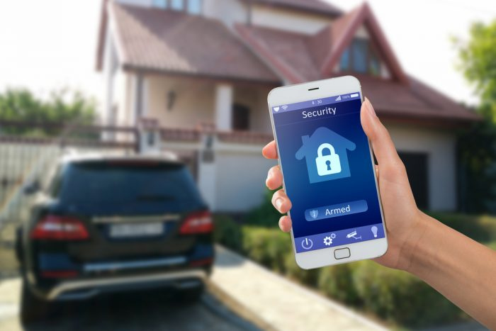 Security app on a cell phone being held in front of a house